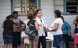 Minister within the Ministry of Indigenous Peoples' Affairs, Valerie Garrido- Lowe interacting with a resident of River's View (GINA photo)