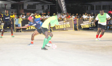 East Front Road's Kacy John (blue vest) trying to maintain possession of the ball while being challenged by West Front Road's Hubert Pedro while Randolph Wagner of Wets Front Road look on during their team's matchup in the Guinness of the Streets Georgetown Zone at the Albouystown Tarmac