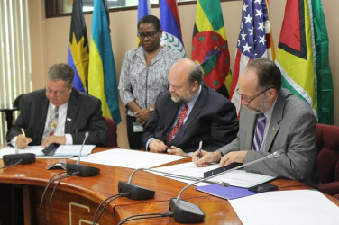 USAID's Eastern and Southern Caribbean Mission Director Christopher Cushing (at left) and Caricom Secretary General Irwin LaRocque signing the aid agreement while US Ambassador Perry Holloway (centre) looks on.