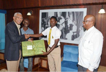 President David Granger presents Terron Alleyne with a new laptop computer, as Minister of Finance, Winston Jordan (right), and the lad's father, Terrence Alleyne, looks on. (GINA photo) ​