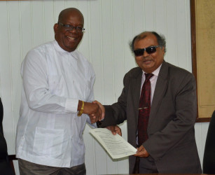 Minister of Finance Winston Jordan (left) and Fedders Lloyd Country Representative Ajay Jha shaking hands on the deal. (Ministry of Finance photo)