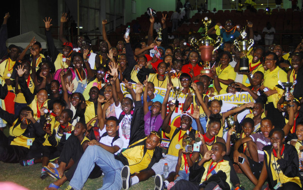 Athletes and officials of Upper Demerara/Kwakwani celebrating last night at the National Stadium with their Champions of Champions trophy which was presented by Digicel's Louanna Abrams. (Orlando Charles photo)