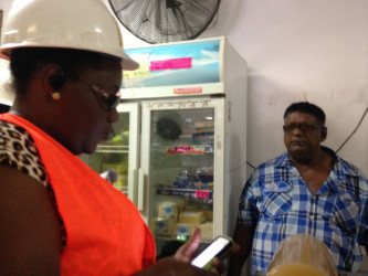 Junior Social Protection Minister Simona Broomes speaks with the owner of the M Ali and Sons Supermarket