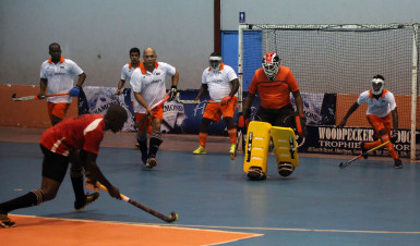 Old Fort's Aderemi Simon (centre) in the process of attempting a penalty corner strike while GCC try desperately to thwart his effort during their team's matchup in the Diamond Mineral Water Hockey Festival at the National Gymnasium