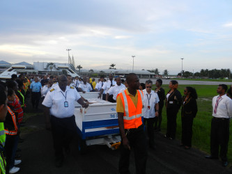 The body of late Captain Alvin Winston Clarke is led through an honour passage at the Cheddi Jagan International Airport yesterday. (Roraima Airways Inc photo)