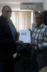 Minister of Governance Raphael Trotman receiving the petition from rights activist Karen de Souza on behalf of the Justice for Walter Rodney Campaign. (Justice for Walter Rodney Campaign photo)