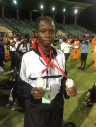 Track star in the making Kenisha Phillips proudly displays the two gold medals she won at the just concluded 2015 National School's Cycling, Swimming and Track and Field Championships en route to breaking both records.