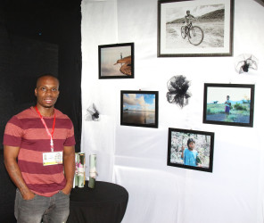 Photographer Brian Gomes showcases some of his other framed photos which were on sale at his booth at the Business Expo.