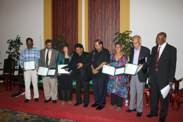 Prime Minister, Moses Nagamootoo (fifth from left) is flanked by from (left to right) Subraj Singh, Stanley Niamatali, Maggie Harris, David Dabydeen, Barbara Jenkins, Eddie Baugh and Al Creighton who represented Harold A. Bascom.
