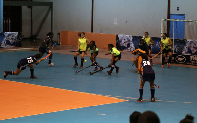 Sonia Jardine (centre) of Pizza Hut GCC in the process of scoring a penalty corner during her side's crushing win over Hikers in the Diamond Mineral Water Hockey Festival at the National Gymnasium.