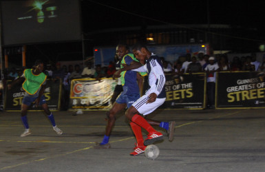Kemo Smith (right) of Albouystown-A trying to maintain possession of the ball while being challenged by a North East La Penitence player during the latter's hard-fought win at the Demerara Park Tarmac in the Guinness Greatest of the Streets Georgetown Championship.