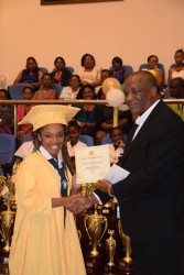 Minister of State, Joseph Harmon handing over a certificate and $50,000 cheque to Shontay Noel on President David Granger's behalf. Noel graduated from the St. Roses High School earlier today. The ceremony was held at the Arthur Chung Convention Centre. (GINA photo)