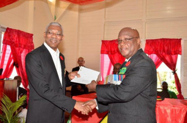 President David Granger (left) handing over cheques in the amount of $4.8M to President of the Guyana Veterans Legion, Lt. Col. (ret'd), George Gomes (GINA photo)