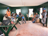 Workers listen to Minister Simona Broomes in their lunch room at the Kurubuka mining site