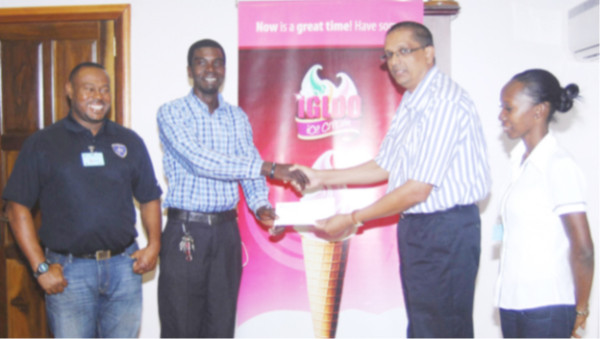 Petra Organization representative Mark Alleyne collecting the sponsorship cheque from Sterling Products Managing Director Ramsay Ali (2nd from right) while Petra Organization Director Troy Mendonca (left) and President of the Guyana Women's Association Charmaine Wade look on.