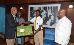 President David Granger presents Terron Alleyne with a new laptop computer, as Minister of Finance, Winston Jordan (right), and the lad's father, Terrence Alleyne, looks on