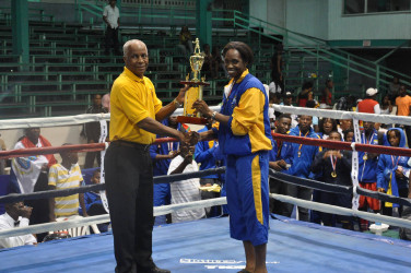 Barbados' Kimberley Gittens receiving her female best boxer trophy of the Caribbean Development Goodwill Tournament which concluded Sunday night at the Cliff Anderson Sports Hall.