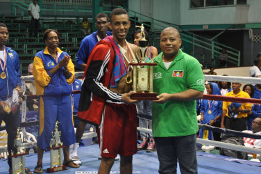 Trinidad and Tobago's Aaron Hackett receiving his best boxer award when the curtains came down on the Caribbean Development Goodwill Tournament Sunday night at the Cliff Anderson Sports Hall