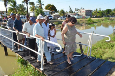 Minister of Social Cohesion Amna Ally (right) and residents on the bridge constructed by the De Kinderen Community Group (GINA photo)