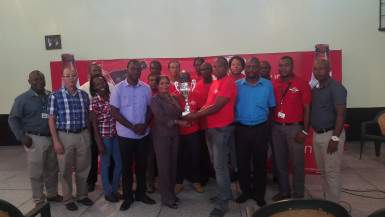 Banks DIH Limited captain Seon McKenzie collecting the championship trophy from the Ministry of Tourism PRO representative Marjorie Chester while other members of the team, the respective sponsors and the coordinating team looks on