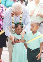 Minister of Education, Dr Rupert Roopnaraine with pupils of the Cummings Park Nursery at the symbolic cutting of the ribbon (Ministry of Education photo)