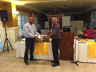 Dr Kenneth Jainandan (left) handing over the supplies to Ron Robinson