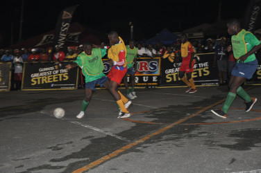 Jamal Haynes of West Back Road (second from left) battling with a North Ruimveldt player for possession of the ball during the latter's round-of-16 win in the Guinness of the Streets Georgetown Championship at the National Cultural Centre Tarmac