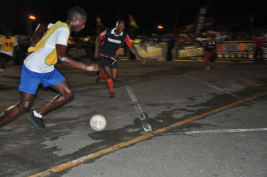 Okeene Fraser (right) of Bent Street in the process of attempting a challenge on the attacking Andrew Murray Jr. of Old School Ballers during their round of 16 showdown in the Guinness of the Streets Georgetown Championship at the National Cultural Centre Tarmac