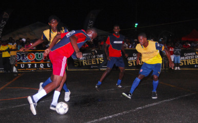 Dennis Edwards (blue vest) of Channel-9 Warriors trying to control the ball while being challenged by Jamal Pedro of West Front Road as teammate Delon Williams (centre) and opposing player Hubert Pedro (right) look on.