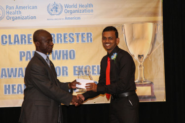Stabroek News Reporter David Papannah collecting his prize for Best News Story Online.