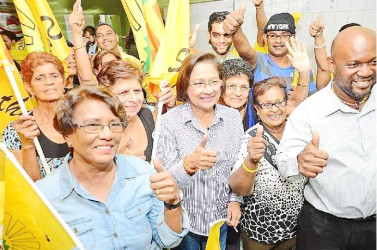 Re- elected United National Congress ( UNC) political leader Kamla Persad-Bissessar (centre) celebrates with supporters following her victory in the UNC internal election at her Penal constituency office on Saturday night.