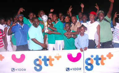 GTT Representative Eusi Francis (front row, second from left) handing over the championship trophy to Milerock captain Joel McKinnon while members and supporters of the team celebrate their hard-fought win over Victoria Kings in the GTT/Limacol Football Championship at the Mackenzie Sports Club ground