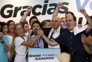 Lilian Tintori (centre L), wife of jailed Venezuelan opposition leader Leopoldo Lopez, celebrates next to candidates of the Venezuelan coalition of opposition parties (MUD) during a news conference on the election in Caracas, December 7, 2015. (Reuters/Carlos Garcia Rawlins)