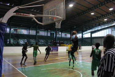 Zion Gray of Tutorial High in the process of scoring against the Bishops High during their u-15 encounter in the YBG Youth-Level Championship at the Cliff Anderson Sports Hall
