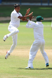 Gudakesh Motie celebrates with Leon Johnson after he took a wicket (WICB photo)