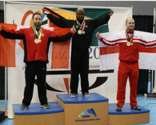 Karel Mars is draped with the Golden Arrowhead atop the podium after lifting a total of 817kgs, good enough for the Commonwealth gold in the 105kg Men's Open Class.