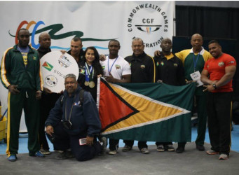 Guyana's medal heist squad posing with the Golden Arrowhead at the 6th Commonwealth Powerlifting Championships which concluded in Vancouver, Canada on Sunday.