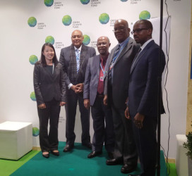 Minister Raphael Trotman (second from left) with the team from Global Green Initiative after the signing.(Ministry of the Presidency photo)