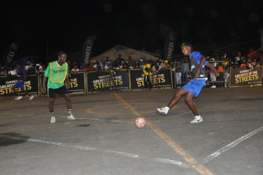 Gregory Richardson (right) of Sparta Boss in the process of attempting a forward pass while being marked by North Ruimveldt's Travis Grant during their team's semi-final encounter at the National Cultural Centre Tarmac in the Guinness of the Streets Georgetown Championship.