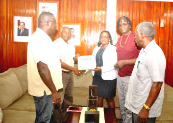 GCAG representatives receiving their Certificate of Registration from Minister Simona Broomes.