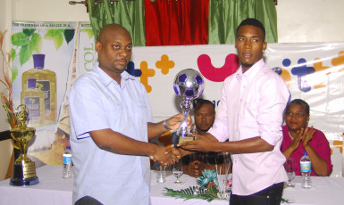 Clarence Huggins (right) of Milerock FC collecting his Most Valuable Player accolade from Limacol Finance Director Duane Lovell during the official Limacol/GTT Football Championship presentation ceremony.