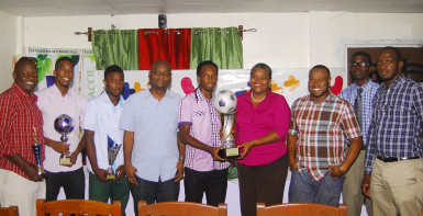 Captain of the victorious Milerock FC Joel McKinnon (centre) receiving the championship trophy from GTT PRO Allison Parker during the official Limacol/GTT Football Championship presentation ceremony while other members of his team, respective prize winners, sponsors and Petra Organization staff look on.