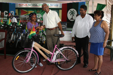 President David Granger presenting a bicycle to one of the children enrolled in the Sophia Literacy Programme at Congress Place yesterday, while Minister of Social Cohesion Amna Ally (right) and GAICO boss Komal Singh, who donated the bicycles to the Boats, Bicycles and Buses school transportation programme, look on. (Photo by Keno George)
