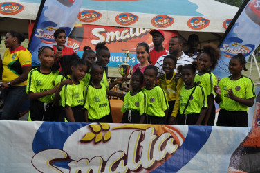 Newly-minted winners St Stephens collecting the championship trophy from ANSA McAL Brand Manager Anjeta Hinds (centre) following their penalty shoot-out win over Stella Maris in the 2nd Smalta/Ministry of Public Health Girls U-11 Football Championship.