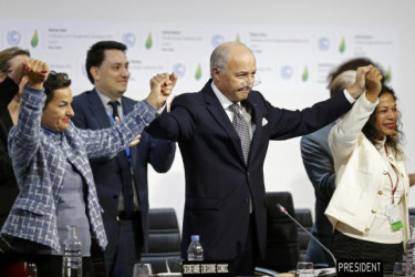 French Foreign Affairs Minister Laurent Fabius (C), President-designate of COP21 and Christiana Figueres (L), Executive Secretary of the UN Framework Convention on Climate Change, hold hands as they react during the final plenary session at the World Climate Change. (Reuters/Stephane Mahe)