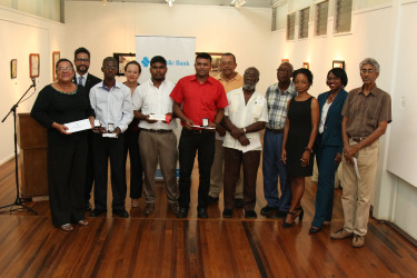 """Artists along with the representatives of the Castellani House Management Committee,  Republic Bank and the Department of Culture at Castellani House yesterday, where the results of the Tenth Biennial National Drawing Competition were announced. Standing from left are artist Josefa Tamayo, who received the bronze medal for """"Cannonball Flowers,"""" and artist Kwesi Archer, who received the silver medal for his entry, """"The Yellow Girl."""" The gold medal winner, Walter Gobin, was not present. (Keno George photo)"""