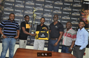 Sparta Boss captain Devon Millington (2nd from left) collects the championship trophy and package from Guinness Representative Shawn Stephney while other members of Banks DIH and Petra Organization including Guinness Brand Manager Lee Baptiste (3rd from right) and Petra Organization Director Troy Mendonca (left) look on.
