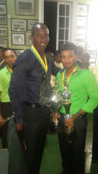 Guyana Jaguars Left-arm spinner Veerasammy Permaul strikes a pose with the team's Assistant Coach Rayon Griffith last evening. Permaul copped the Guyana Cricket Board (2015) Male Cricketer of the Year award as well as the Rohan Kanhai Trophy for the Senior Regional Cricketer of the Year 2015.