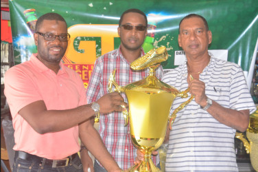 UDFA President Sharma Solomon receives the first place trophy from Ramesh Sunich of Trophy Stall while Jeoff Clement GT Beer Brand manager looks on.