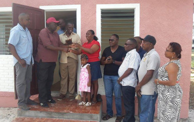 Natasha Dash receiving the keys to her newly renovated house yesterday from Eswick Northe of The Garage, while other members of the community who helped make it possible look on
